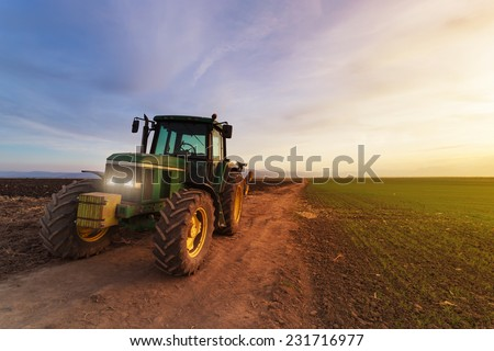 Green tractor on field at sunset after plowing