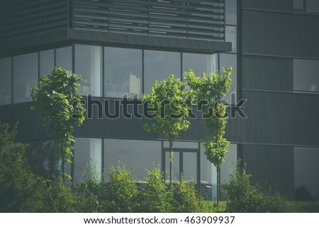 Green trees in front of a black office building
