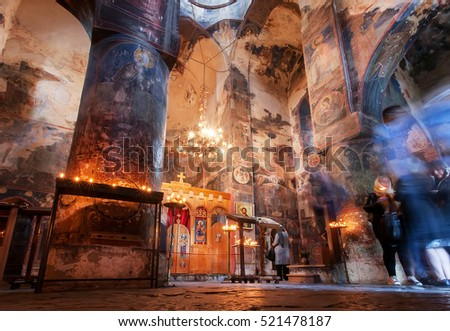 GREMI, GEORGIA - OCT 1: People praying with candles in dark interior of Church of the Archangels with frescoes on 1 October, 2016. The Curch was built in 16th century in Kakheti, Georgia.