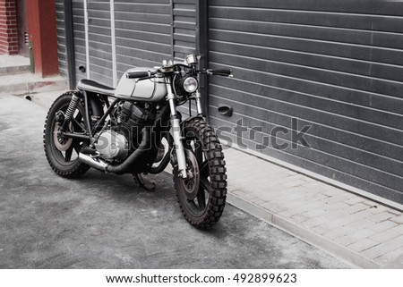 Grey rebuilt motorcycle cafe racer in front of rolled gates of garage. Wild lifestyle
