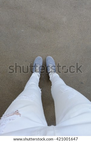 Grey Sneakers On Girl Legs On Ground Great For Any Use.