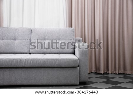 Grey sofa against curtains in the room