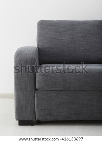 Grey sofa isolated against the wall