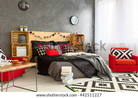 Grey spacious bedroom with big bed with grey and black blankets and red pillows. Next to it red armchairs and wooden coffee table