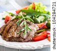 Grilled beef steak with salad and rosemary sprig - stock photo