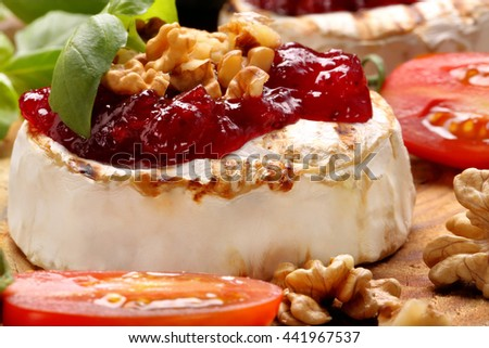 Grilled brie cheese with cranberry jam and walnuts on old wooden background