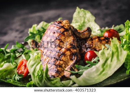 Grilled chicken breast in different variations with lettuce salad cherry tomatoes  mushrooms herbs cut lemon on a wooden board or teflon pan. Traditional cuisine. Grill kitchen.