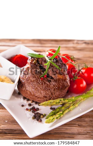 Grilled meat with fresh vegetable on wooden table