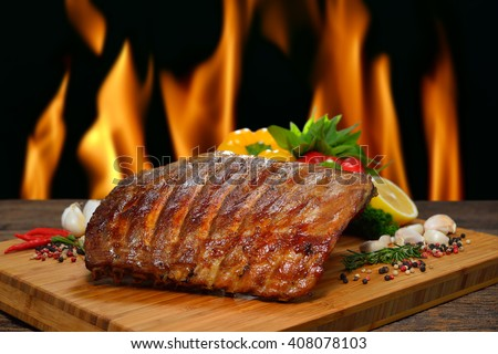 Grilled pork ribs and various vegetables on a chopping wood