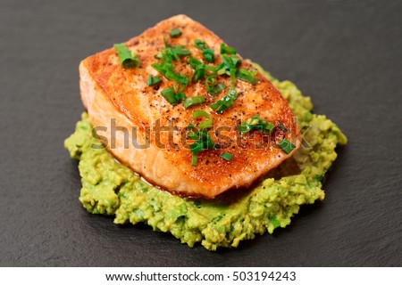 Grilled salmon fillet with avocado mash and green leek on slate plate