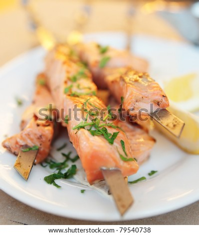 Grilled salmon on metal sticks on porcelain plate