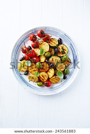 Grilled spiced vegetables with olives on a plate