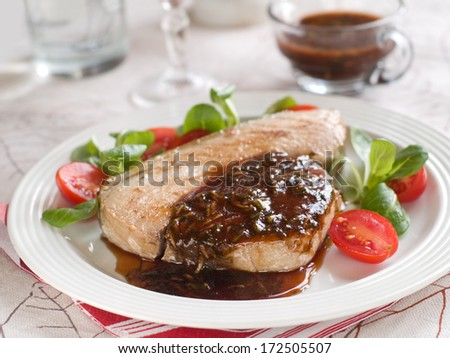 Grilled tuna steak with sauce and salad, selective focus