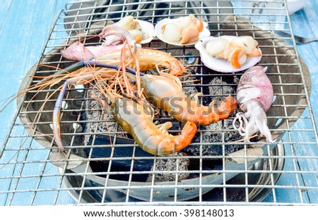 Grilling seafood on blue painted wooden table, Close up image