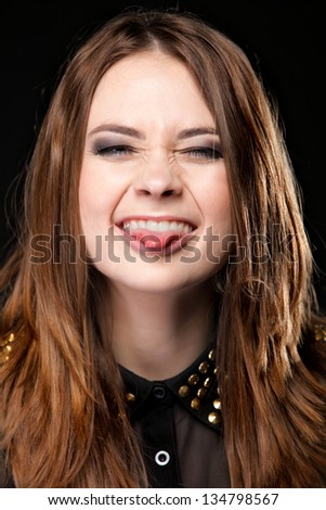 Grimacing young woman making silly face sticking out her tongue on black background