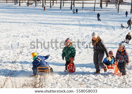 GRODNO, BELARUS - DEC 04: Families enjoy sledding on a snowy hill in a city Park at December 04, 2016 in Grodno, Belarus