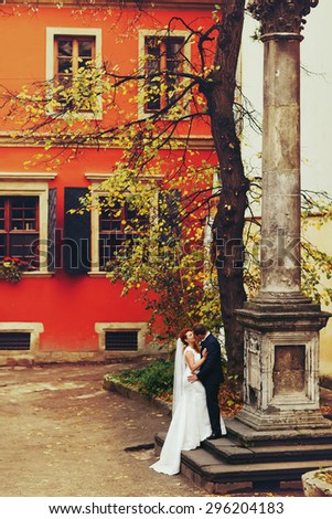 grom hugging bride with red hair outdoors background red wall  Lviv