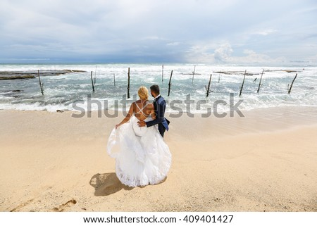 groom and bride posing on the beach on a tropical island
