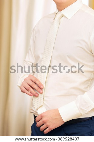 groom dresses cuff links on cuffs