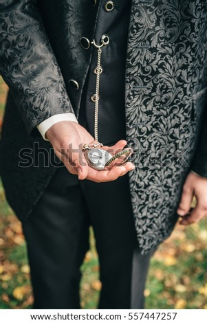 Groom holding an old pocket watch in his hands. Maybe he is waiting for his bride