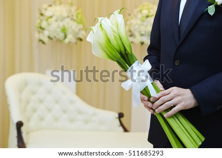 Groom holding flower bouquet