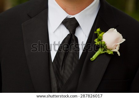 Groom wearing a boutonniere consisting of a rose and hypericum at a wedding.
