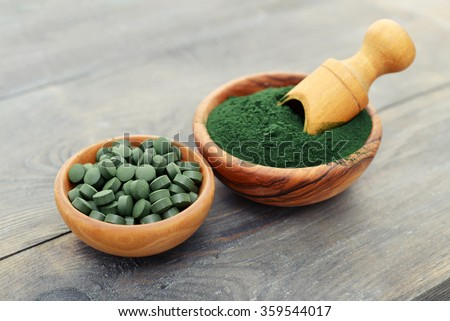Ground spirulina and spirulina in pills over black wooden background