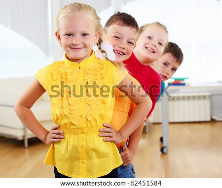 Group classmates standing in a row in the classroom