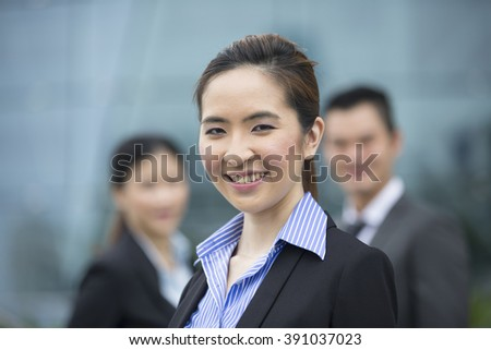 Group of Asian business people with woman leader in foreground. Chinese business woman leading her team.
