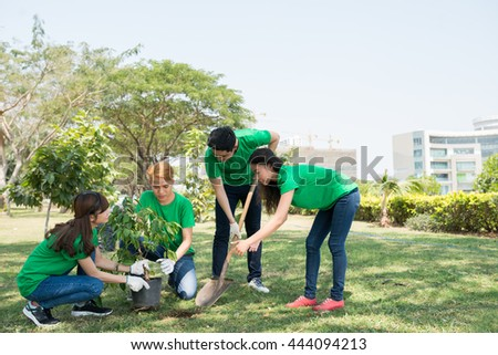 Group of Asian young people planting trees in city park