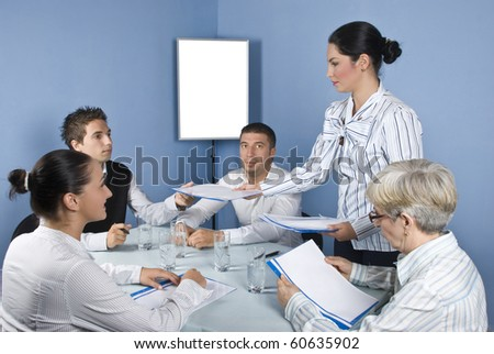 Group of  business people at meeting table sitting on chair while a business young woman giving all folders with papers