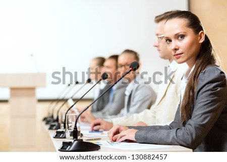group of business people sitting at the tables at the presentation, woman looking at the camera