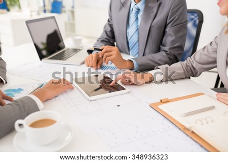 Group of business people using digital tablet during business meeting