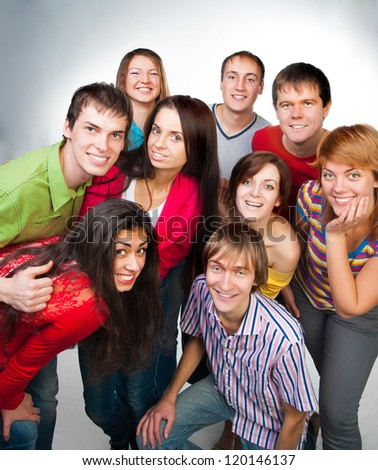 group of casual happy people smiling and standing over a light background