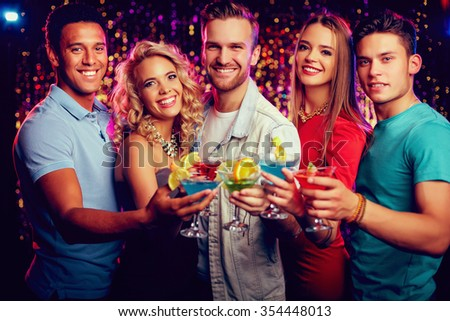 Group of cheerful friends toasting with cocktails at party