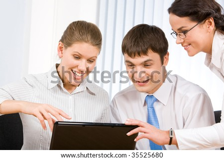 Group of co-workers looking at laptop monitor while happy female pointing at it