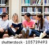Group of college students at the library looking happy - stock photo