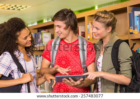 Group of college students using digital tablet in the library