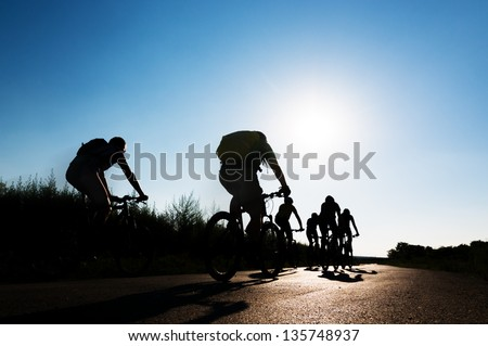 group of cyclists biking in motion