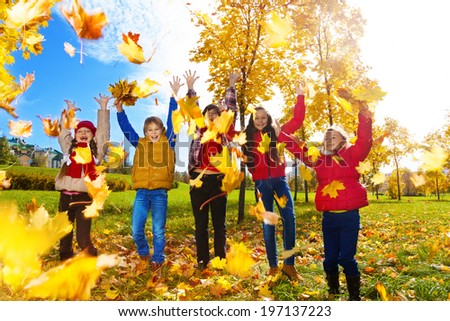 Group of five kids, boys and girls throwing autumn maple leaves in the park on sunny day