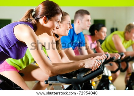 Group of five people in gym or fitness club exercising their legs doing cardio training