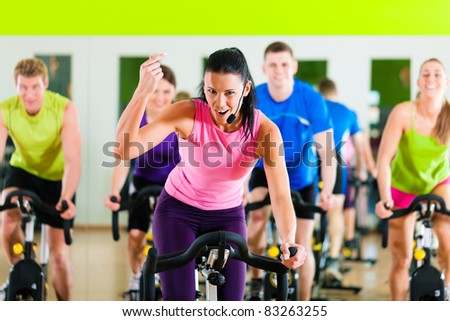 Group of five people - men and women - in gym or fitness club exercising their legs doing cardio training; the trainer is in front
