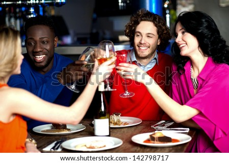 Group of four friends raising a toast