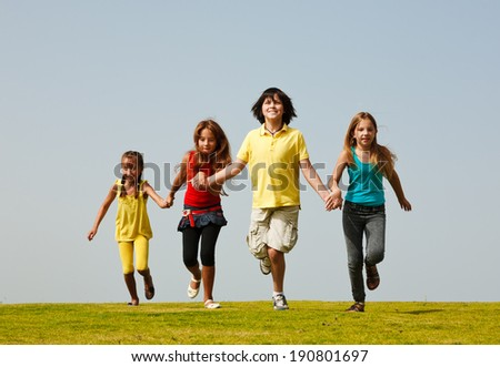 Group of four  happy children running outdoors.