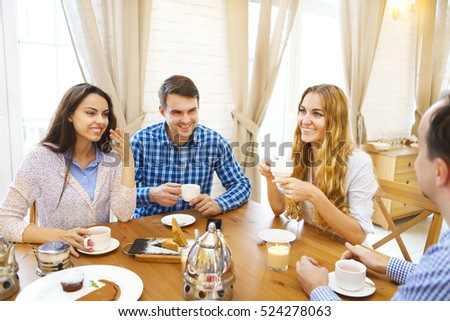 Group of four happy friends meeting and talking and eating desserts on a table at home