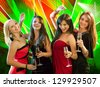Group of four stylish women standing in a row toasting with flutes of champagne - stock photo