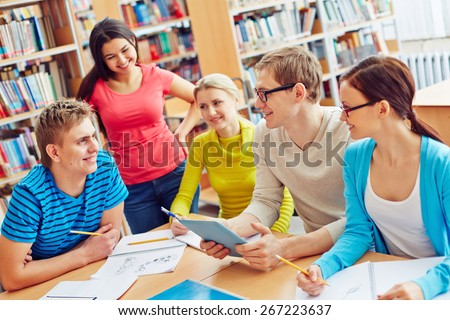 Group of friendly students sitting in college library and communicating