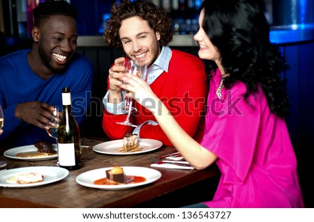 Group of friends having their dinner with drinks at a restaurant.