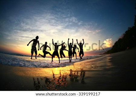 Group of friends jumping for joy on tropical beach at sunset