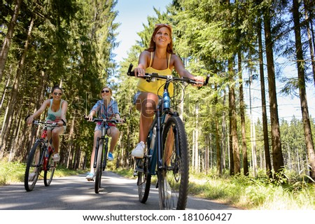 Group of friends on bicycles in countryside enjoy summer sport